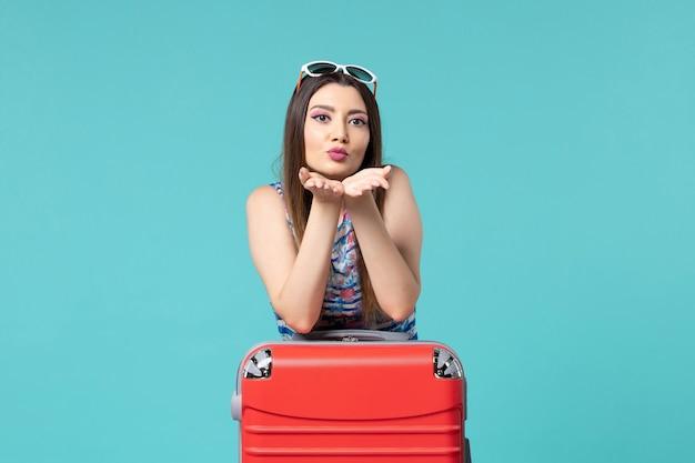 Vista frontal linda mulher se preparando para as férias com bolsa vermelha no espaço azul claro