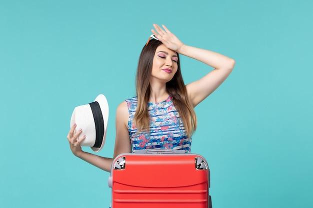 Vista frontal linda mulher se preparando para as férias com bolsa vermelha no piso azul, viagem, viagem, férias, mar, viagem