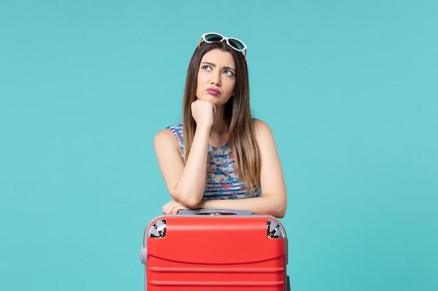 Vista frontal linda mulher se preparando para as férias e pensando no espaço azul