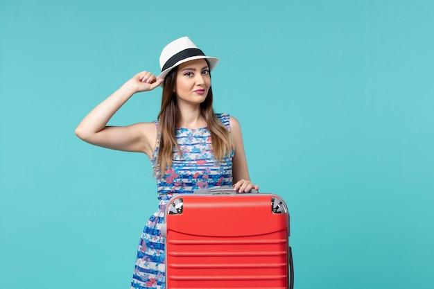 Vista frontal linda mulher se preparando para as férias e posando em um espaço azul claro