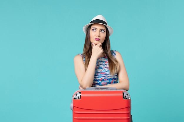 Vista frontal linda mulher se preparando para as férias e posando pensando no espaço azul
