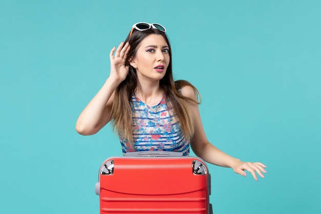 Vista frontal linda mulher se preparando para as férias e tentando ouvir no espaço azul