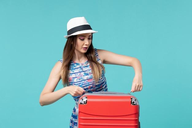 Vista frontal linda mulher se preparando para as férias, posando no espaço azul