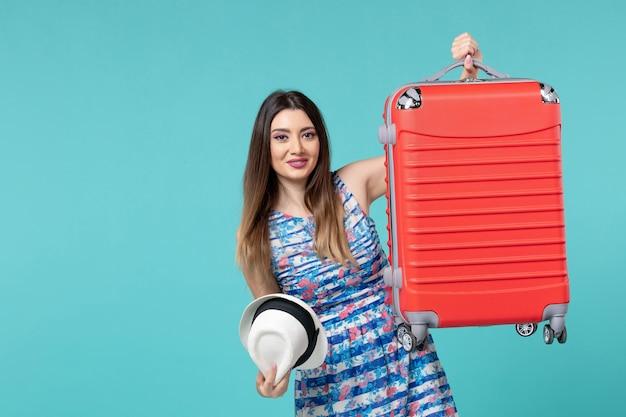 Vista frontal linda mulher segurando uma bolsa vermelha e se preparando para uma viagem no espaço azul