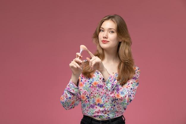 Vista frontal linda senhora apontando seu pincel de pó cosmético