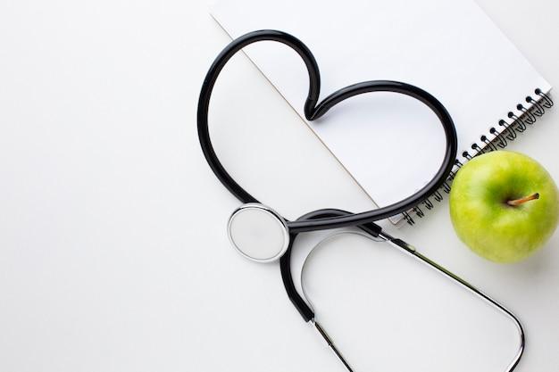 Vista frontal maçã verde e estetoscópio em forma de coração