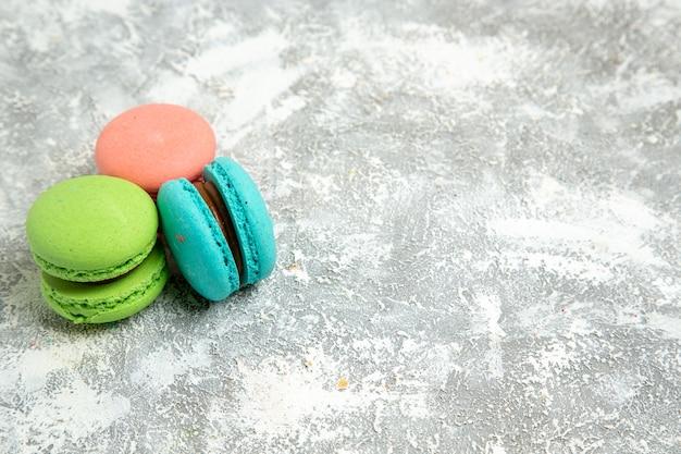 Vista frontal, macarons franceses, bolos coloridos na superfície branca, torta, bolo, biscoito doce, biscoito