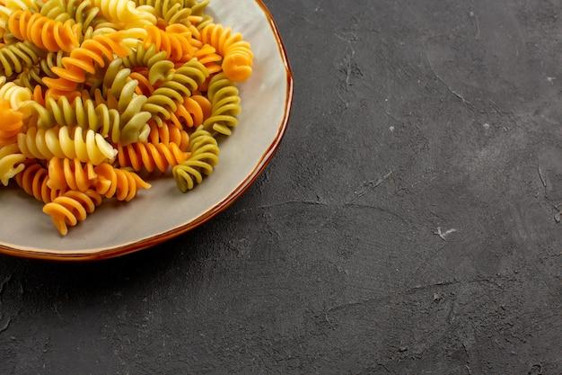 Vista frontal macarrão italiano cozido macarrão espiral incomum dentro do prato na mesa escura