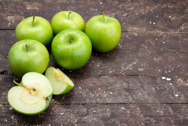 Vista frontal maçãs verdes frescas fatiadas e inteiras no escuro
