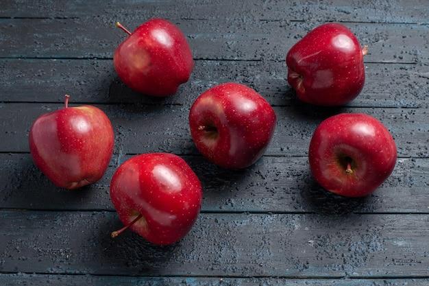 Vista frontal, maçãs vermelhas frescas, frutas maduras e suaves em azul escuro.