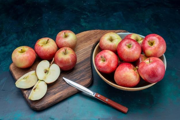 Vista frontal, maçãs vermelhas frescas suculentas e maduras dentro do prato na superfície azul escura frutas maduras frescas