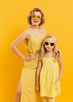 Vista frontal mãe e filha com óculos de sol