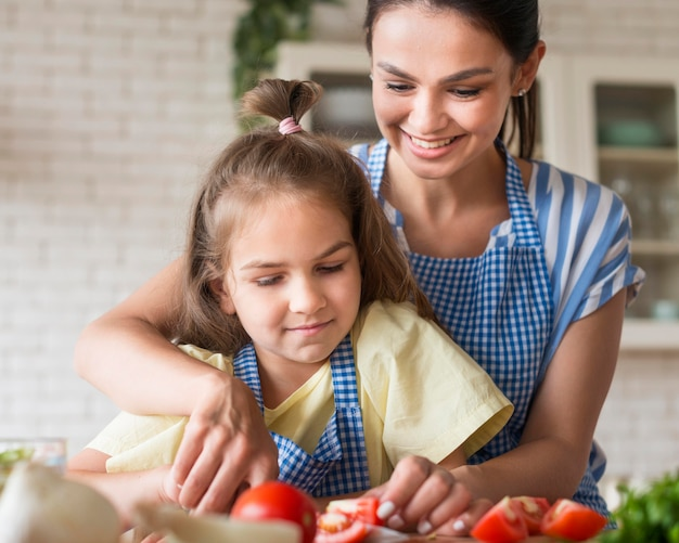 Vista frontal mãe e filha cozinhar
