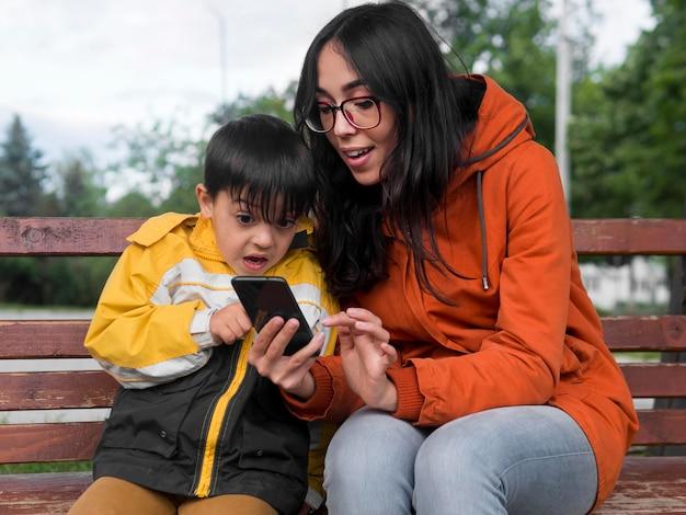 Vista frontal mãe e filho usando o telefone celular
