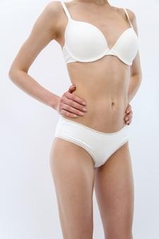 Vista frontal. magro jovem desportiva em lingerie branca mostra sua figura