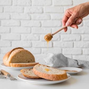 Vista frontal mão derramando mel sobre fatia de pão