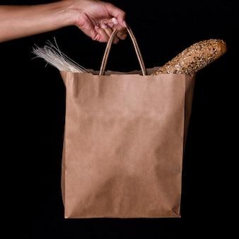Vista frontal, mão segurando sacola com pão