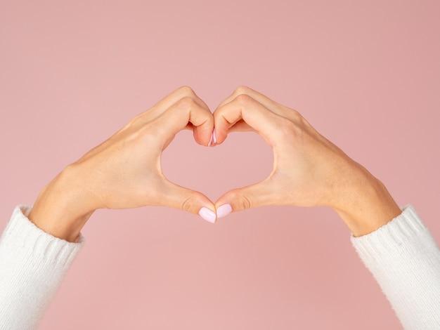 Vista frontal mãos mostrando o gesto do coração