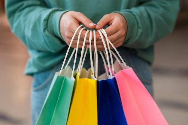 Vista frontal mãos segurando sacos de papel colorido