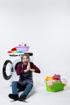 Vista frontal maravilhada governanta do sexo masculino juntando as mãos sentados em frente ao cesto de roupa suja da máquina de lavar no fundo branco