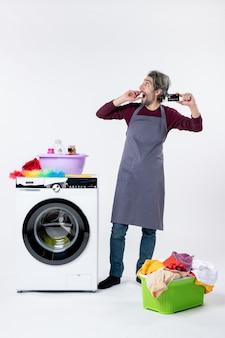 Vista frontal maravilhada, segurando um cartão em pé perto da máquina de lavar, no fundo branco