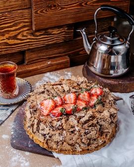 Vista frontal marrom bolo de chocolate com morangos frescos vermelhos por cima e chá quente no chão marrom