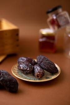 Vista frontal marrom saboroso xurma dentro da placa na mesa de madeira