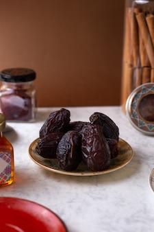 Vista frontal marrom xurma doce querida oriental dentro do prato na mesa branca