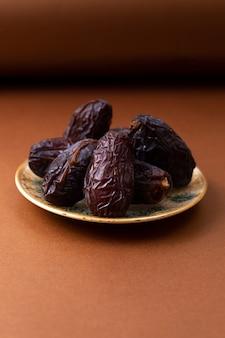 Vista frontal marrom xurma doce saboroso dentro da placa na mesa de madeira marrom