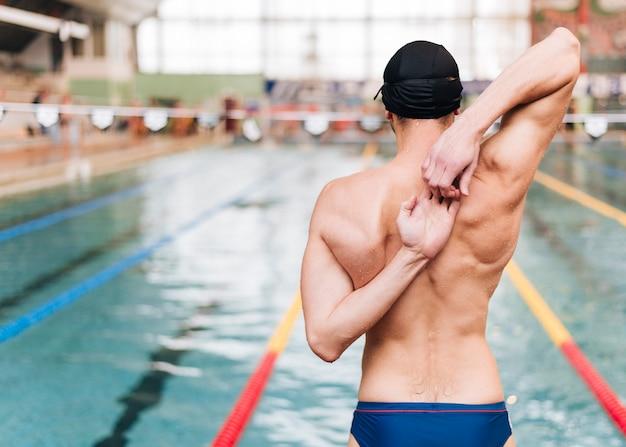 Vista frontal masculino alongamento antes de nadar