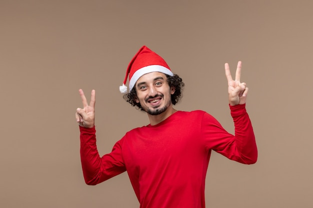 Vista frontal masculino em vermelho com rosto sorridente em fundo marrom férias emoção natal