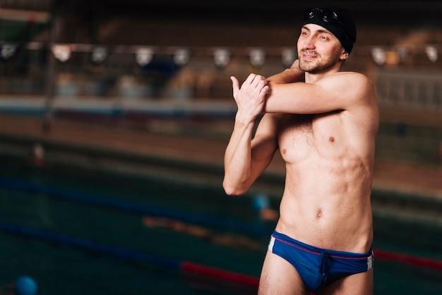 Vista frontal masculino nadador alongamento