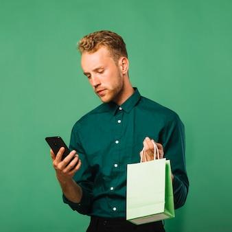 Vista frontal masculino, verificando seu telefone