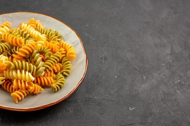 Vista frontal massa italiana cozida em espiral incomum dentro de um prato no espaço escuro