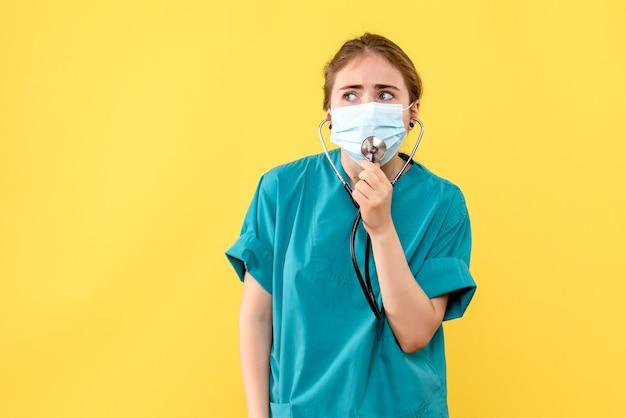 Vista frontal médica com máscara na mesa amarela, vírus da saúde, pandemia covid