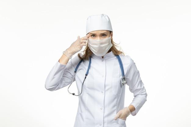 Vista frontal médica em traje médico com máscara e luvas devido ao coronavírus na doença de parede branca-clara covide pandêmica