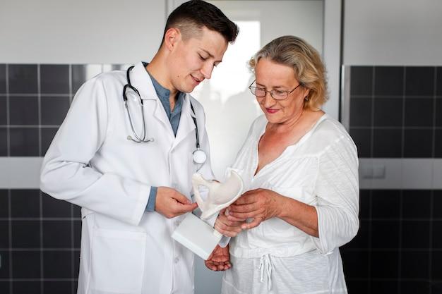 Vista frontal médico e paciente olhando para um pedaço de osso