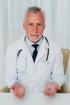 Vista frontal médico segurando comprimidos nas mãos
