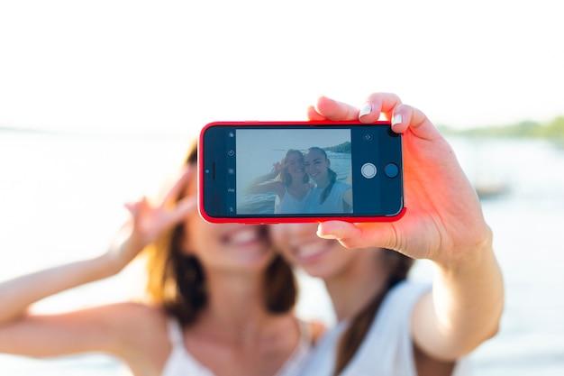 Vista frontal melhores amigas tirando uma selfie