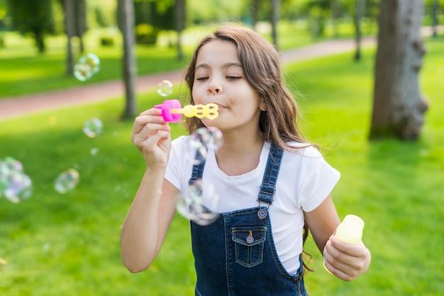 Vista frontal menina bonitinha fazendo bolhas de sabão