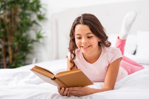 Vista frontal menina bonitinha lendo histórias