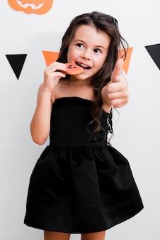 Vista frontal menina comendo um biscoito
