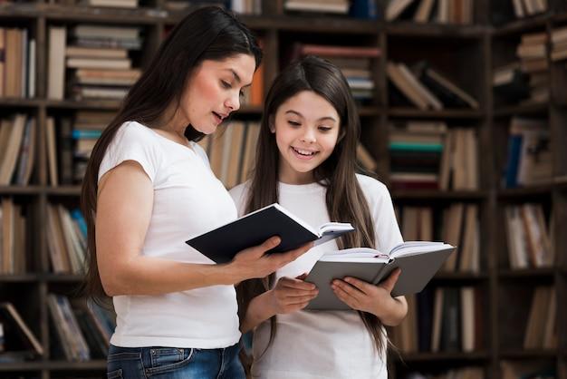 Vista frontal menina e mulher lendo livros