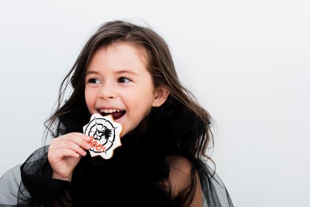 Vista frontal menina feliz comendo um biscoito