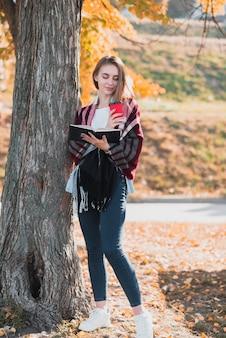 Vista frontal menina loira segurando um caderno