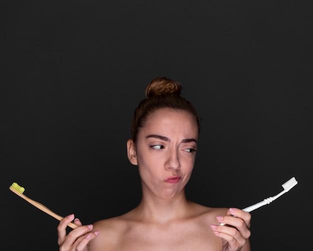 Vista frontal, menina, segurando, escovas de dentes