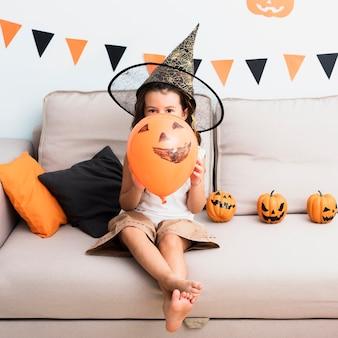 Vista frontal menina segurando um balão de halloween