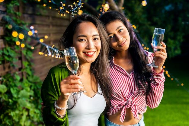 Vista frontal meninas jovens com taças de champanhe