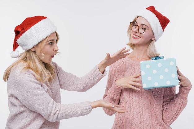 Vista frontal meninas segurando um presente