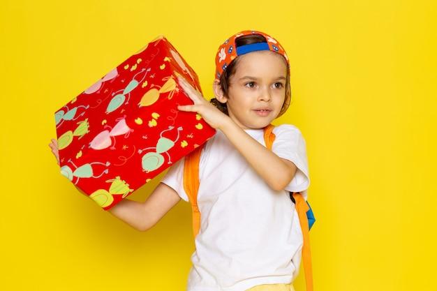Vista frontal menino bonitinho na camiseta branca segurando vermelho projetado presente na mesa amarela